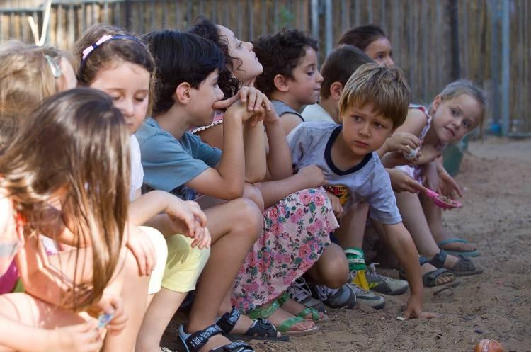 Avi Shnaidman entre los niños de una escena