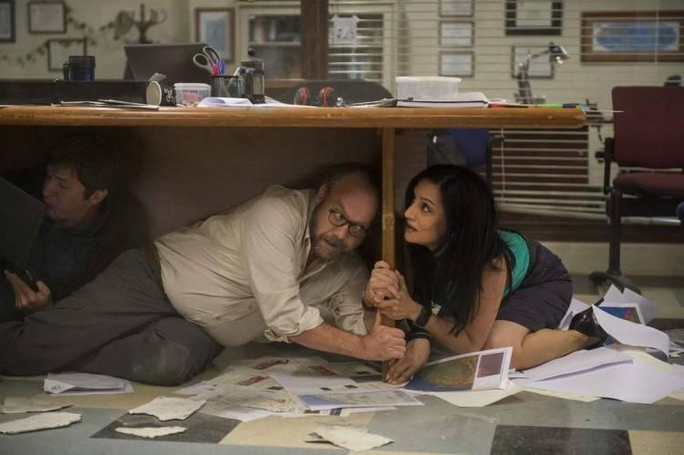 Paul Giamatti y Archie Panjabi protegiéndose de un terremoto
