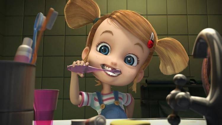 Una niña se limpia los dientes.