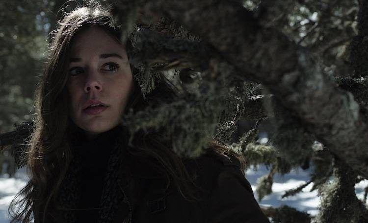 Laia Costa parece espiar a alguien en el bosque
