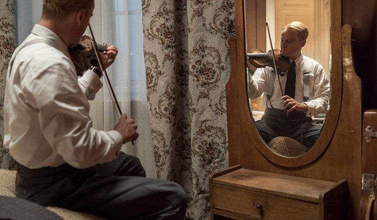 Jason Clarke en una escena tocando el violín
