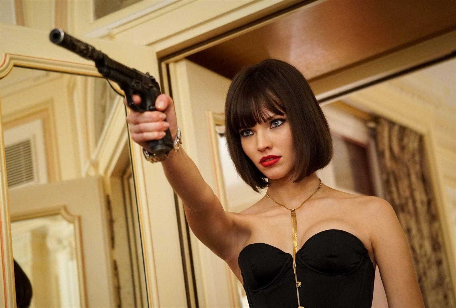 La protagonista, Anna, tras la dirección de Luc Besson, apunta con un arma a un objetivo que se encuentra fuera de plano. Viste ropa negra.
