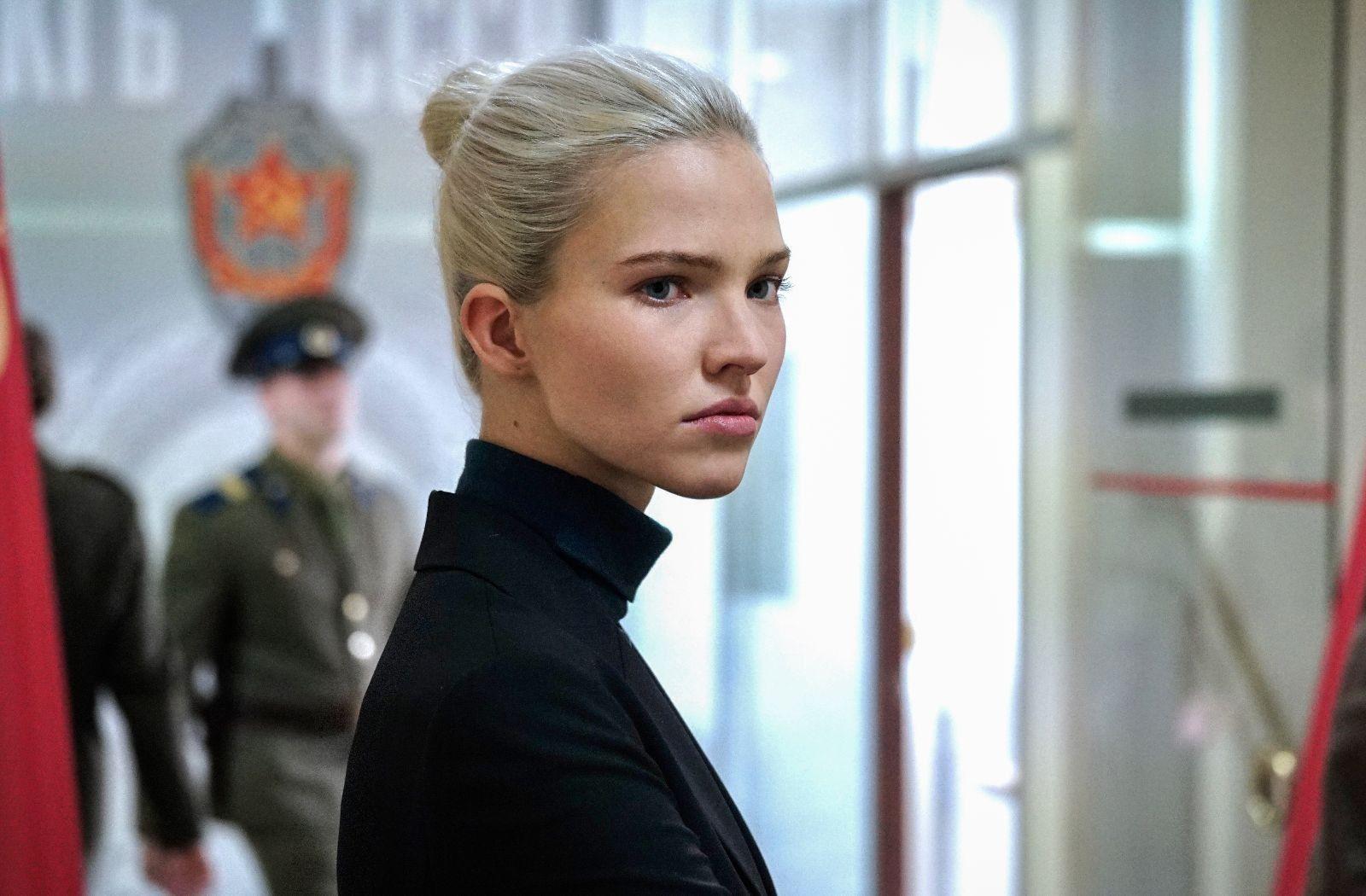 La protagonista, Anna, bajo la dirección de Luc Besson, viste ropas negras de cuello alto, lleva el pelo recogido. Mira a su derecha, mientras que a su espalda circulan dos agentes de policía rusos.