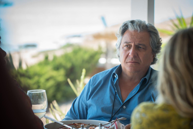 El personaje Philippe mira al horizonte sentado en una terraza. Viste una camisa azul, delante suyo hay un plato con comida, y una copa de cristal.