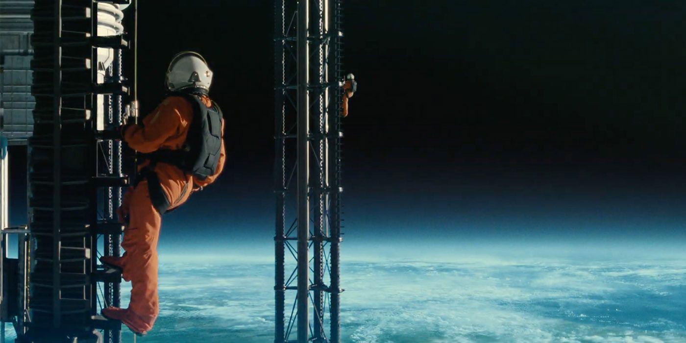Dos astronautas aparecen en la imagen, ambos visten rojas de astronautas color naranja. Se encuentran fuera del globo terráqueo, por lo que se puede ver en la imagen, parecen estar en una infraestructura espacial, en ese momento se encuentran en una especie de escalera, debajo de ellos, a miles de kilómetros, la Tierra.