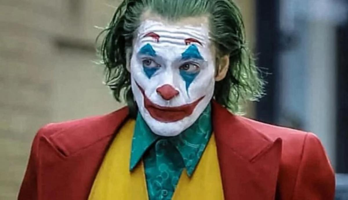 En la imagen se puede ver al Joker de Joaquin Phoenix, viste una chaqueta naranja, chaleco amarillo, y una camisa verde. Tiene la cara pintada como un payaso, aunque su mirada parece estar buscando algo que se encuentra fuera de plano